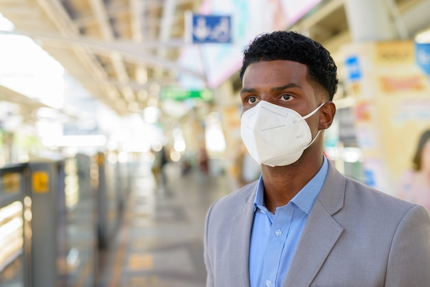 African businessman at train station platform wearing face mask while waiting train