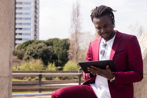 도시, 기술 및 원격 작업 개념에서 야외에서 태블릿에 입력하는 아프리카 사업가