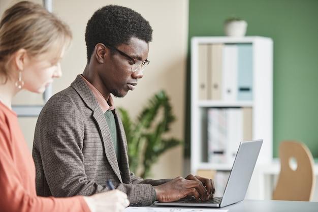 彼の同僚がオフィスのテーブルで彼の近くに座ってラップトップで入力するアフリカのビジネスマン