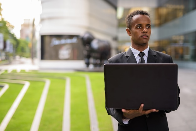 Африканский бизнесмен, используя портативный компьютер, думая на открытом воздухе