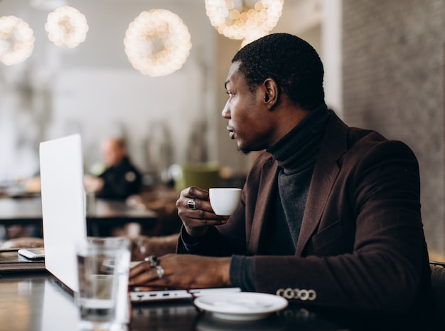 African businessman using phone and drinking coffee while working on laptop in a restaurant.