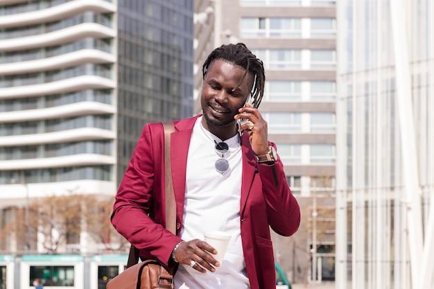 아프리카 사업가가 손에 커피를 들고 전화 통화를 하며 도시를 걷는다