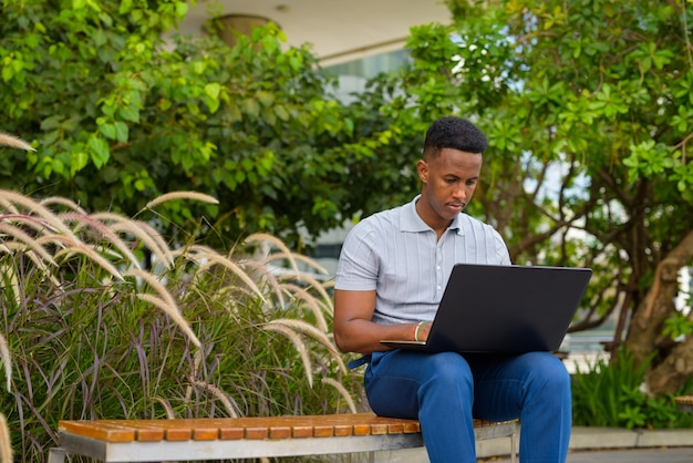 African businessman wearing casual clothes and sitting while using laptop computer