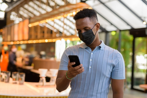 African businessman wearing face mask in coffee shop restaurant while social distancing and using mobile phone