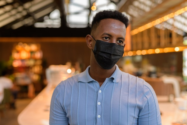 African businessman wearing face mask in coffee shop restaurant while thinking