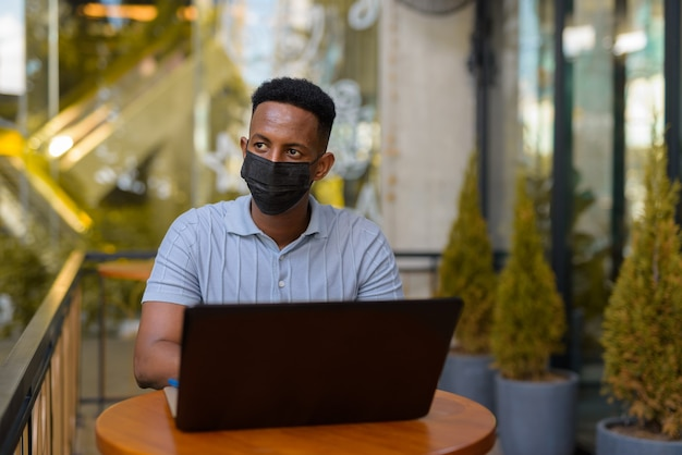 African businessman wearing face mask and social distancing while sitting at coffee shop using laptop computer
