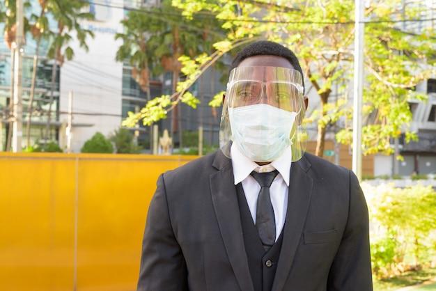 屋外の街のバス停でマスクと顔のシールドを持つアフリカの実業家
