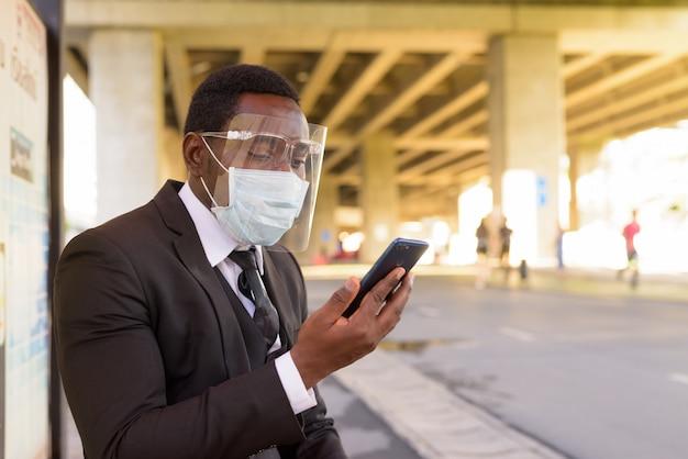 屋外のバス停で電話を使用してマスクと顔のシールドを持つアフリカの実業家