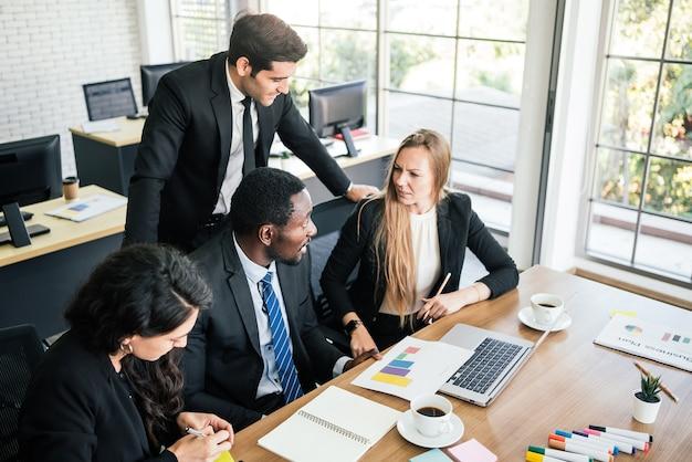 Африканские бизнесмены сидят среди кавказских коллег, глядя на ноутбук на встрече внутренней бизнес-группы. разнообразие сотрудничества деловых людей.