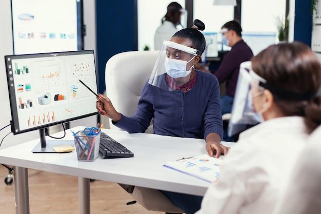 フェイスマスクを身に着けている公式でカラフルなグラフを分析するアフリカの実業家。コロナウイルスによる世界的大流行のため、社会的距離を尊重する新しい通常の会社で働く多民族チーム。