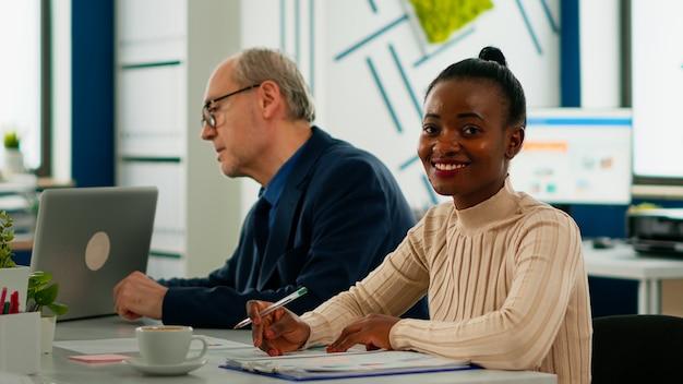 ブレーンストーミング中に会議デスクに座ってレポートを分析し、カメラの笑顔を見ているアフリカの実業家。専門家で働く起業家は、会議の準備ができて金融ビジネスを開始します