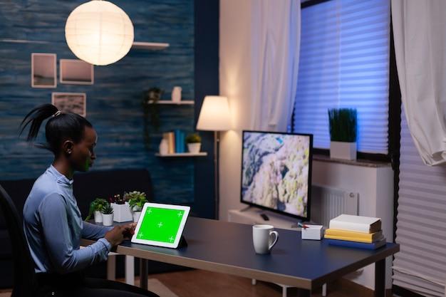책상에 앉아 있는 집 사무실에서 늦은 밤 집에서 일하는 동안 태블릿 pc를 보고 있는 아프리카 여성 사업가입니다. 모형 크로마 키 디스플레이 컴퓨터를 사용합니다.