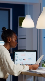 African businesswoman reading business reports from laptop