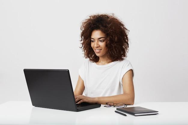 Lavoro sorridente della donna di affari africana al computer portatile sopra la parete bianca.