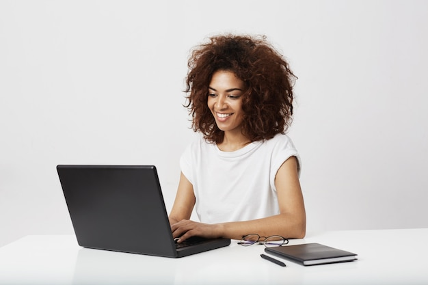 African businesswoman smiling working at laptop over white wall.