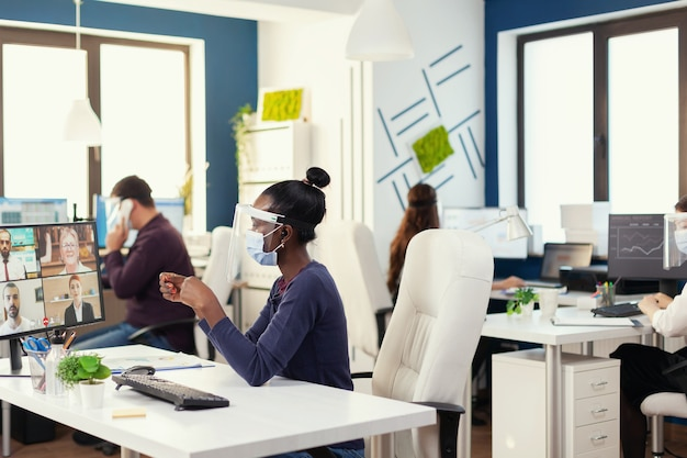 African businesswoman wearing wireless headphones during online call with business people wearing face mask. new normal business office multiethnic team working respecting social distance during globa