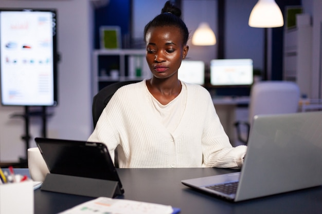 African businesswoman working late at night in office using tablet pc
