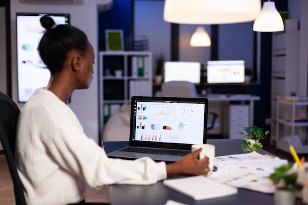 늦은 밤 사무실에서 재정 통계 작업을 하는 아프리카 여성