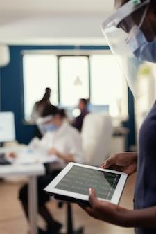 Африканская деловая женщина смотрит на график и использует планшетный пк в маске для лица против covid19. многонациональные коллеги уважают социальную дистанцию в деловой компании во время глобальной пандемии коронавируса