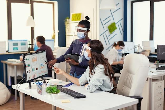 Colleghi africani e caucasici che lavorano insieme indossando la maschera facciale contro il covid19. diversi team che lavorano nel rispetto del distanziamento sociale durante la pandemia globale con il coronavirus. nuova normalità.