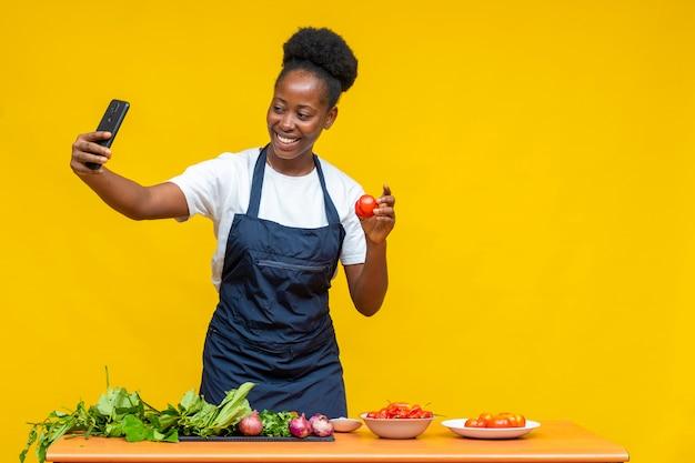 アフリカのシェフがビデオを撮り、電話中の人に食材を見せます