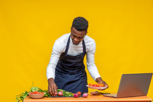 アフリカのシェフが食事を準備し、ラップトップを使用する