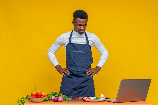 困惑しているように見える料理をしながらラップトップを使用しているアフリカのシェフ