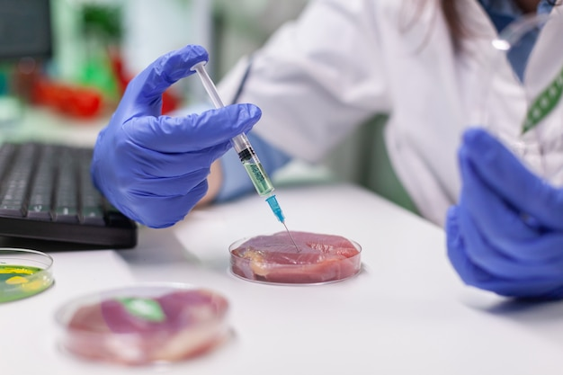 African chemist injecting at lab-grown vegan meat sample for microbiology expertise. scientist woman working on plant-blased beef substitute in biochemistry lab researching modified genetically food.