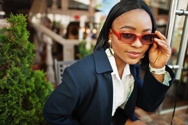 コートとサングラスのアフリカのシックなビジネスの女の子。アフリカ系アメリカ人女性のファッショナブルなストリートポートレート。
