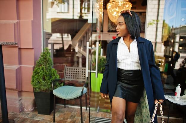 コートを着たアフリカのシックなビジネスの女の子。アフリカ系アメリカ人女性のファッショナブルなストリートポートレート。