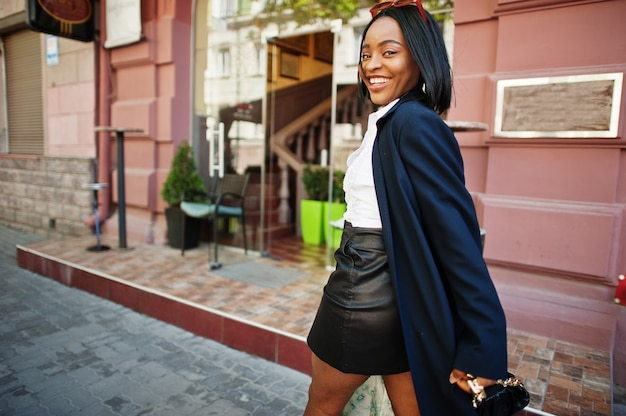 ハンドバッグのコートでアフリカのシックなビジネスの女の子。アフリカ系アメリカ人女性のファッショナブルなストリートポートレート。