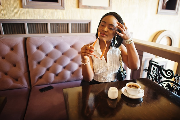 白いブラウスと黒い革のスカートを持つアフリカのシックな女の子。カフェに座ってコーヒーを飲むファッショナブルなアフリカ系アメリカ人の女性。