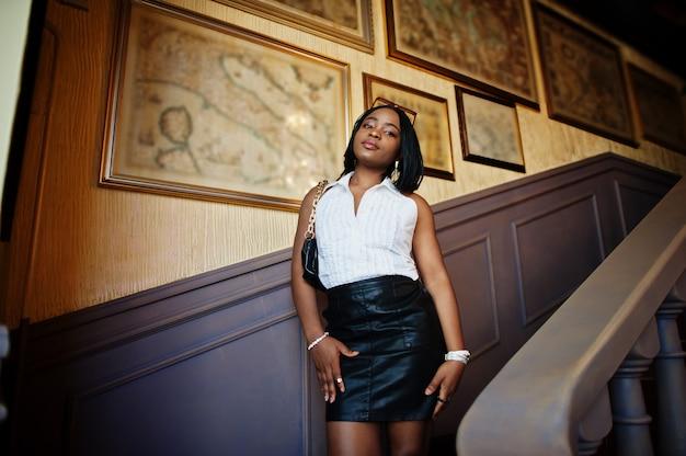 白いブラウスと黒い革のスカートを持つアフリカのシックな女の子。ファッショナブルなアフリカ系アメリカ人の女性。