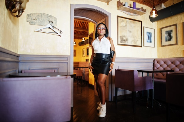 白いブラウス、黒い革のスカートと白いスニーカーを持つアフリカのシックな女の子。ファッショナブルなアフリカ系アメリカ人の女性。 Premium写真