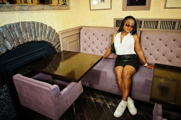 白いブラウス、黒い革のスカートと白いスニーカーを持つアフリカのシックな女の子。ファッショナブルなアフリカ系アメリカ人の女性。