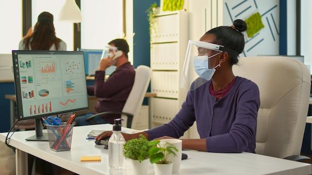 コンピューターでフェイスマスクを書き、社会的距離を尊重する新しい通常のビジネス金融事務所でカメラを見ているアフリカの会社のマネージャー。バックグラウンドで作業している多民族の同僚。