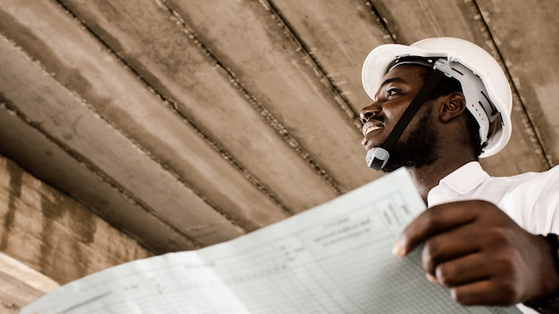African construction engineer looking at blueprints while wearing helmet.16:9 style
