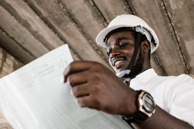 African construction engineer looking at blueprints while wearing helmet