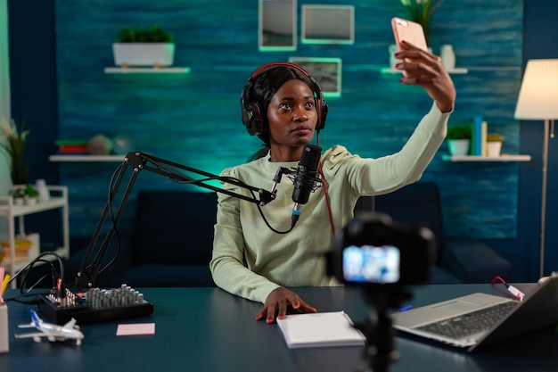 African content creator taking photo with smartphone for fans and recording broadcast. on-air online production internet podcast show host streaming live content, recording digital social media.