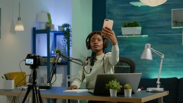 아프리카 콘텐츠 제작자는 팬들을 위해 스마트폰으로 사진을 찍고 방송을 녹화합니다. 온에어 온라인 제작 인터넷 팟캐스트 쇼 호스트 스트리밍 라이브 콘텐츠, 디지털 소셜 미디어 녹음.