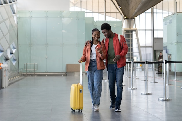 African couple after plane arrival walk with luggage in airport lookin at the smartphone