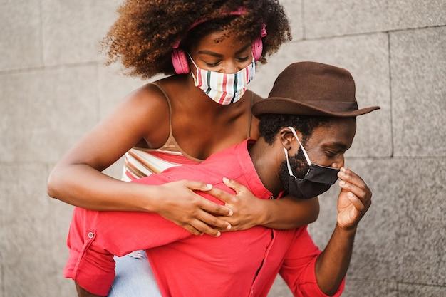 フェイスマスクを身に着けて屋外で楽しんでいるアフリカのカップル-男の目に焦点を当てる
