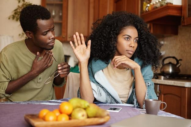 自宅でけんかを持っているアフリカのカップル。不幸な夫が言い訳を受け入れていない怒っている怒っている妻に不倫したことを謝罪する。許しを彼のガールフレンドに懇願する黒人男性