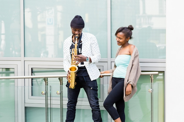 African couple playing saxophone