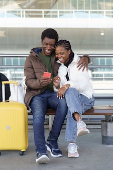 African couple of tourists wait for taxi at airport laughing from funny videos on smartphone Premium Photo