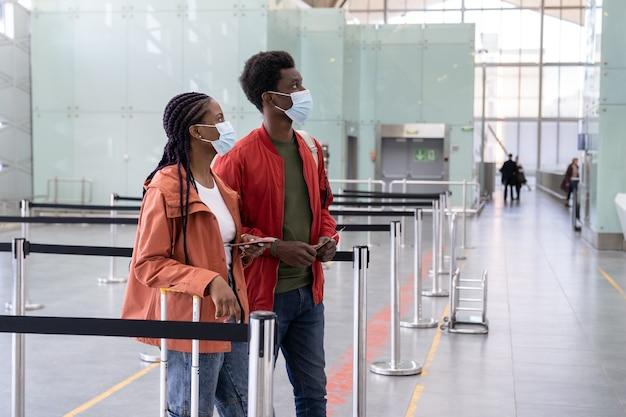 의료 마스크를 착용 한 아프리카 부부는 코로나 바이러스 전염병 동안 공항에서 비행기 탑승을 기다립니다.
