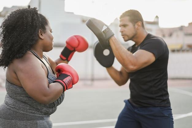 아프리카의 매력적인 여성과 야외에서 권투 운동을 하는 개인 트레이너 - 왼쪽 여자 팔에 초점