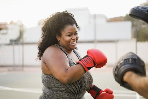 Африканская фигуристая женщина и личный тренер делают тренировку по боксу на открытом воздухе
