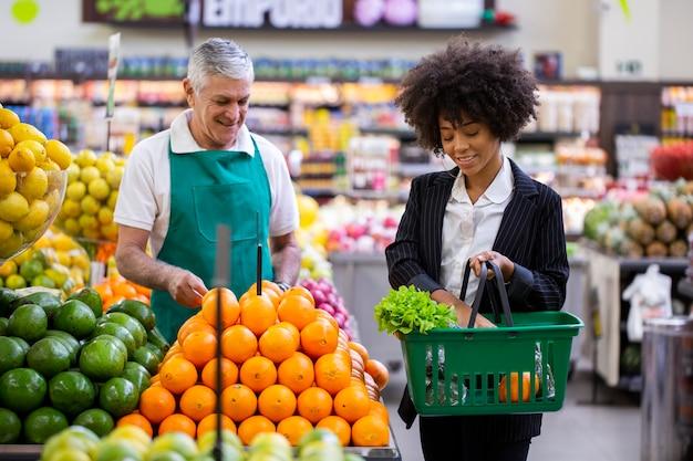 African customer with greengrocer, holding orange fruit.