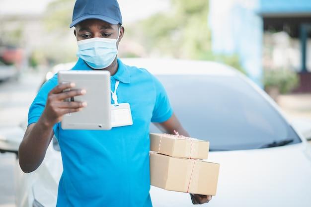フェイスマスクを着用し、ボックスパッケージを保持しているタブレットを探しているアフリカの配達人。検疫配達サービスの概念